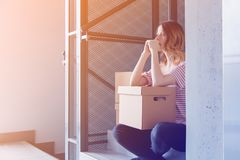 Woman with moving boxes sitting on stairs in house. Young redhead woman with moving boxes sitting on stairs in house. European ethnicity Royalty Free Stock Image