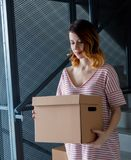 Woman with moving boxes sitting on stairs in house. Young redhead woman with moving boxes sitting on stairs in house. European ethnicity Royalty Free Stock Photos