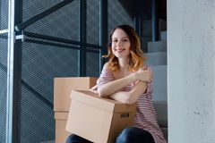 Woman with moving boxes sitting on stairs in house. Young redhead woman with moving boxes sitting on stairs in house. European ethnicity Royalty Free Stock Photography