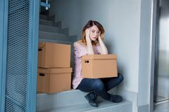 Woman with moving boxes sitting on stairs in house. Young redhead woman with moving boxes sitting on stairs in house. European ethnicity Stock Photos