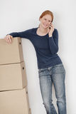 Woman with Moving Boxes Talking on the Phone. A woman resting next to moving boxes and talking on the phone Royalty Free Stock Image
