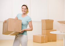 Woman moving cardboard boxes. In new home Royalty Free Stock Images