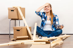 Woman moving in holding screws and furniture parts. Worried woman moving into new apartment house assembling. Young girl holding screws and furniture parts Royalty Free Stock Photo