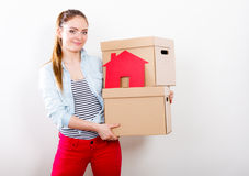 Woman moving into home with boxes and paper house. Stock Photography