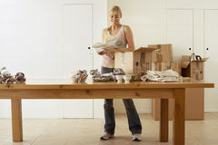 Woman moving house, packing crockery in cardboard boxes on dining room table, smiling, front view Royalty Free Stock Photos