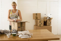 Woman moving house, packing crockery wrapped in paper in box on dining room table, smiling, portrait Royalty Free Stock Photography