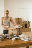 Woman moving house, packing crockery wrapped in paper in box on dining room table, smiling, portrait Royalty Free Stock Photos