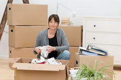 Woman moving house packing her belongings. Kneeling on the floor next to a cardboard box wrapping items in paper Royalty Free Stock Photo