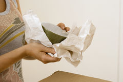 Woman moving house, wrapping crockery in paper, side view, mid-section Royalty Free Stock Image