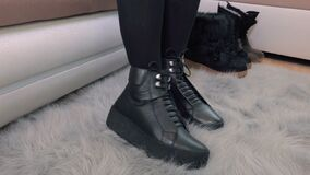 Woman moving legs and checking new boots. In room stock video footage