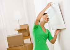 Woman moving into new home hanging picture Stock Image