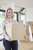 Woman Moving Into New Home With Packing Box Stock Photography
