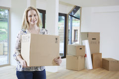 Woman Moving Into New Home With Packing Box Stock Photo