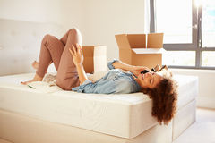 Woman Moving Into New Home Talking On Mobile Phone. In Bedroom Lying Down Stock Images