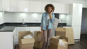 Woman Moving Into New Home Talking On Mobile Phone. Woman unpacking boxes in new home whilst talking on mobile phone. Shot on Sony FS700 in PAL format at a frame stock video