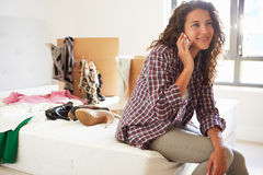 Woman Moving Into New Home Talking On Mobile Phone. Whilst Sitting On Bed Royalty Free Stock Photos