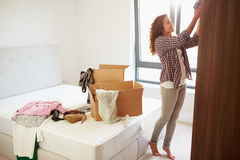 Woman Moving Into New Home And Unpacking Boxes In Bedroom Royalty Free Stock Photo