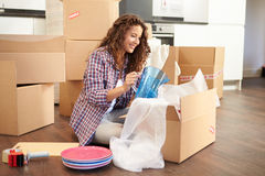 Woman Moving Into New Home And Unpacking Boxes. Holding Object Royalty Free Stock Image