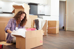 Woman Moving Into New Home And Unpacking Boxes royalty free stock images