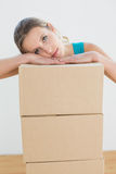 Woman moving in a new house with a stack of boxes Royalty Free Stock Image