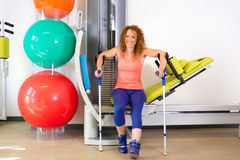 Woman moving off of exercise machine with crutches stock photos