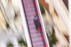 Woman on a moving staircase Stock Images
