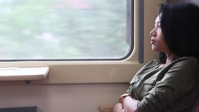 Woman at a moving train. Woman sitting at the window of a moving train stock video