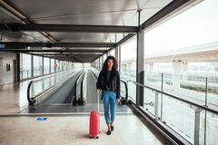 Woman in the moving walkway at the airport with a pink suitcase. Stock Photography