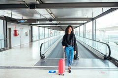 Woman in the moving walkway at the airport with a pink suitcase. Stock Images