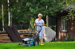 Woman is mowing her lawn with lawn mower Stock Photos