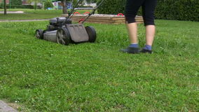 A woman mowing the lawn stock footage