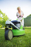 Woman mowing the lawn in garden royalty free stock images