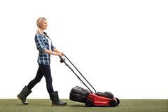 Woman mowing a lawn with a lawnmower Stock Image