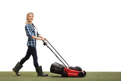 Woman mowing a lawn with a lawnmower Stock Photo