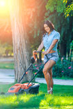 Woman mowing lawn in residential back garden on Stock Images