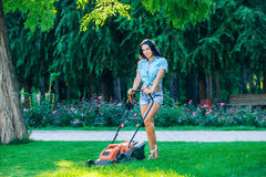 Woman mowing lawn in residential back garden on Royalty Free Stock Photos