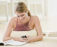 Woman With MP3 Player. A young woman is listening to an mp3 player while looking at a magazine.  She is smilng and looking away from the camera.  Horizontally Stock Image