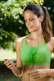 Woman with mp3 player listening to music royalty free stock photography