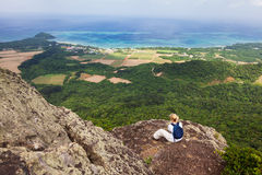 Woman on Mt Nosoko, Ishigaki. A woman sits and admires the coastal view from the top of Mount Nosoko in Ishigaki, Okinawa, Japan Royalty Free Stock Image