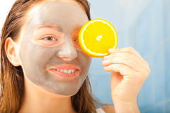 Woman with mud facial mask holds orange slice Stock Images