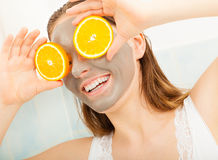 Woman with mud facial mask holds orange slice Stock Photos