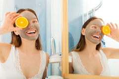 Woman with mud facial mask holds orange slice Stock Photo