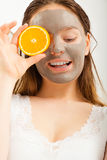 Woman with mud facial mask holds orange slice Royalty Free Stock Images
