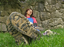 Woman and muddy boots. Portrait of a alone thoughtful attractive brunette woman with a blade of grass in its mouth sitting on the grass with muddy boots that are royalty free stock photos