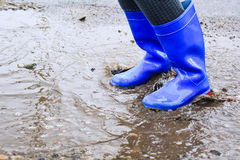 Woman in the muddy puddle in a gumboots Royalty Free Stock Image