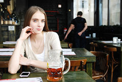Woman with mug of alcohol beer at the cafe Royalty Free Stock Image