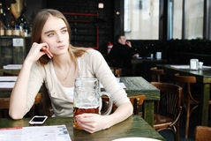 Woman with mug of alcohol beer at the cafe. Pretty young woman with mug of alcohol beer at the cafe Royalty Free Stock Photos