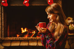 Woman with a mug by the fireplace. Young attractive woman sittin royalty free stock photos