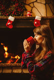 Woman with a mug by the fireplace. Young attractive woman  Stock Photo