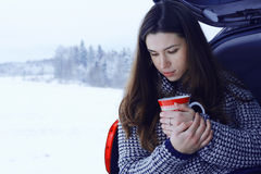 Woman with  mug of hot drink in winter forest Royalty Free Stock Photo